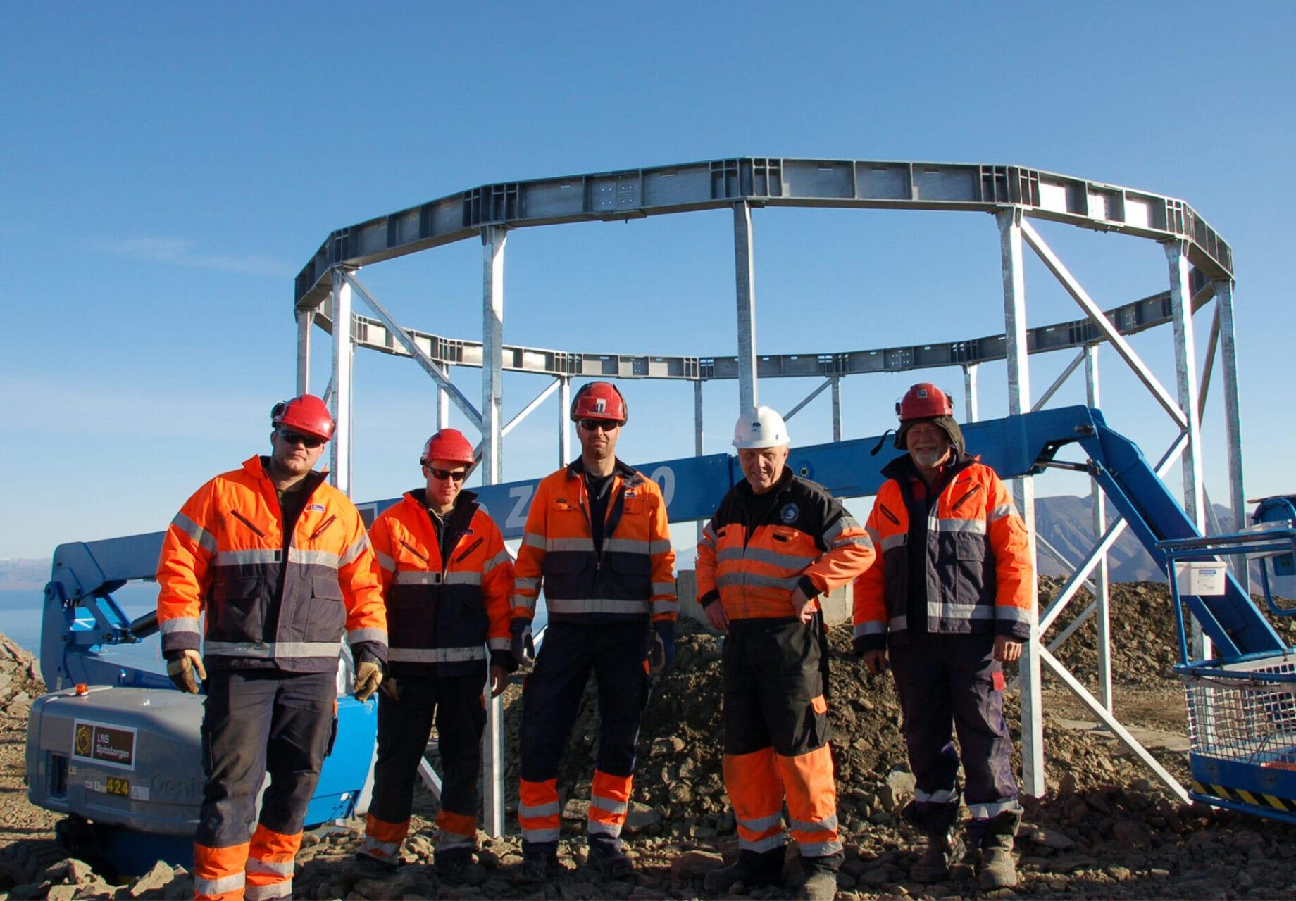 5 arbeidere med orange uniform, hjelm med lys og hørselvern